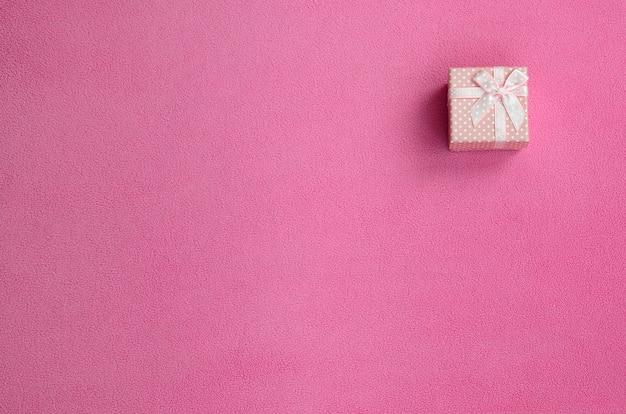Eine kleine geschenkbox in rosa mit einer kleinen schleife liegt auf einer decke aus weichem und pelzigem hellrosa fleece