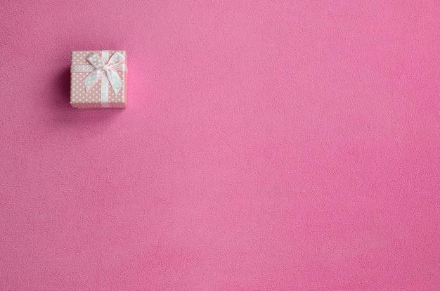 Eine kleine geschenkbox in rosa mit einer kleinen schleife liegt auf einer decke