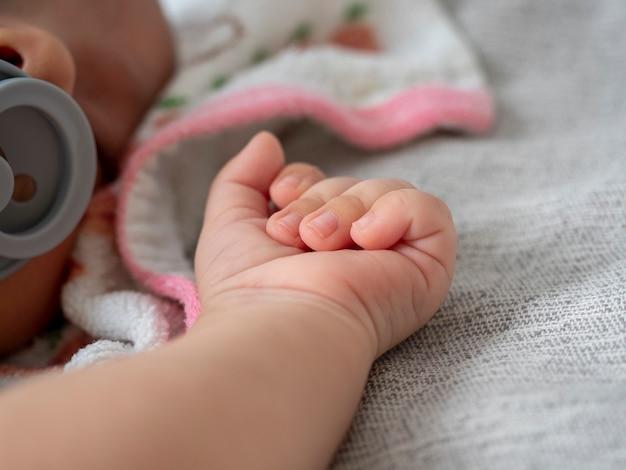 Eine kleine hand eines neugeborenen liegt auf einer grauen decke. kleine kinder