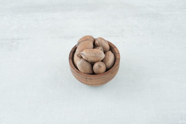 Eine kleine hölzerne schüssel nüsse auf weißem hintergrund. hochwertiges foto