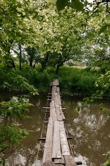Eine kleine holzbrücke über einem milden bach in einem grünen park.