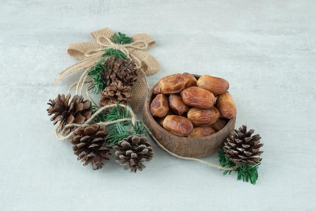 Eine kleine holzschale mit getrockneten früchten und tannenzapfen auf marmorhintergrund. hochwertiges foto