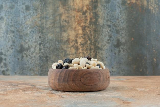 Eine kleine holzschale voller rosinen und nüsse auf marmorhintergrund