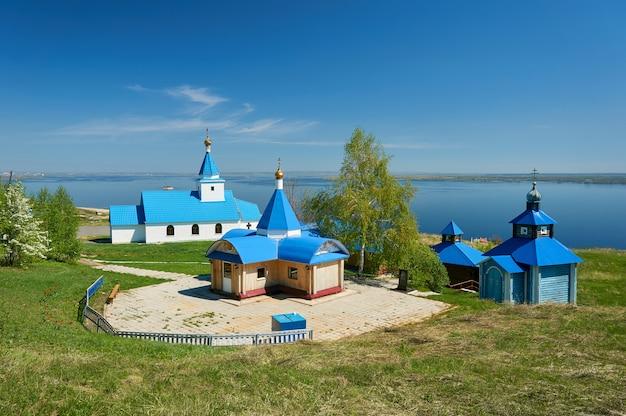 Eine kleine kirche gemalt mit blauer farbe vor dem hintergrund des meeres und des blauen himmels an einem sonnigen tag.