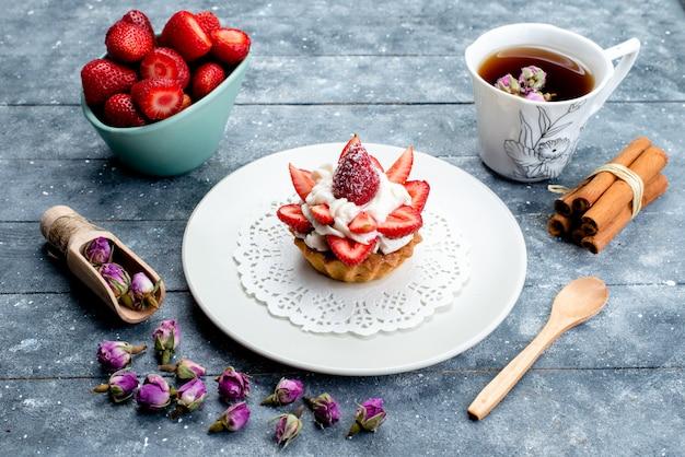 Eine kleine köstliche torte der draufsicht mit sahne-innenplatte mit frisch geschnittenen erdbeeren und tee auf dem blaugrauen hintergrundplätzchenkekskuchen-fruchtzucker-tee