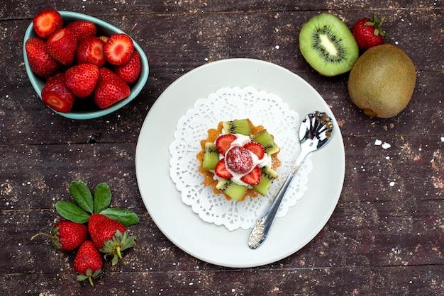 Eine kleine köstliche torte der draufsicht mit sahne-innenplatte mit frischen erdbeeren und kiwis auf der dunklen hintergrundplätzchenkekskuchenfrucht