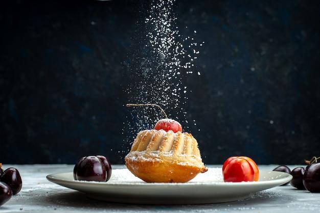 Eine kleine köstliche torte der vorderansicht, die zuckerpulver innerhalb der weißen platte mit kirschen auf der leichten schreibtischkuchen-kekszuckerbeere erhält