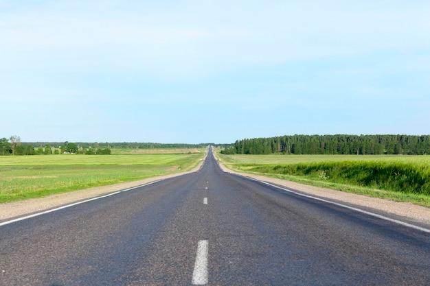 Eine kleine ländliche asphaltstraße. landschaft mit blauem himmel, gras und bäumen. auf der straße bewegen sich autos