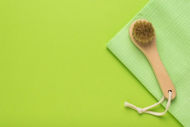 Eine kleine massagebürste auf einem grünen handtuch auf grünem hintergrund.