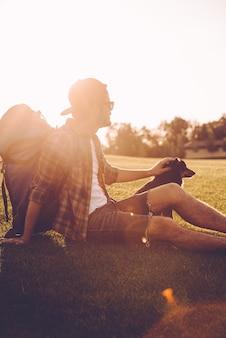 Eine kleine pause machen. selbstbewusster junger mann mit rucksack, der hund streichelt, während er auf grünem gras sitzt