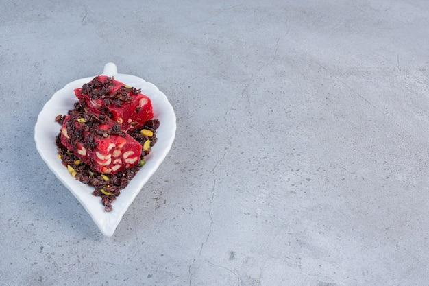 Eine kleine platte mit aromatisierten und farbigen türkischen köstlichkeiten auf marmorhintergrund.