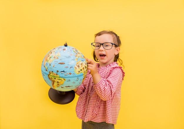 Eine kleine schülerin in brille und kariertem hemd studiert einen globus auf gelb