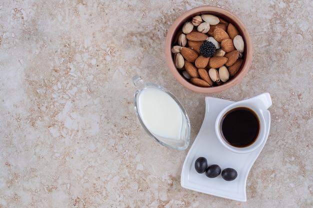 Eine kleine schüssel milch neben einer schüssel mit verschiedenen nüssen und einer tasse kaffee