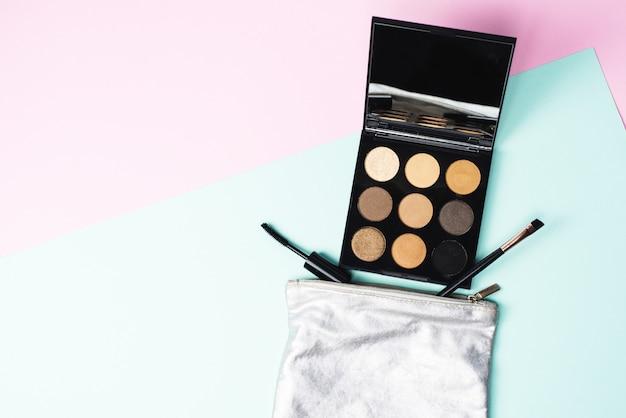 Eine kleine silberne kosmetiktasche mit einer großen schwarzen palette, einem mascara-pinsel und einem pinsel auf rosa hintergrund