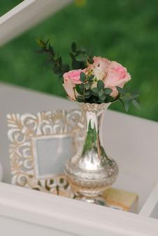 Eine kleine silberne vase mit rosa rosenblüten und grünen zweigen und einem fotorahmen