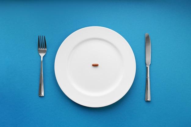 Eine kleine tablette in einem teller. medizinisches konzept. iss pillen statt essen.