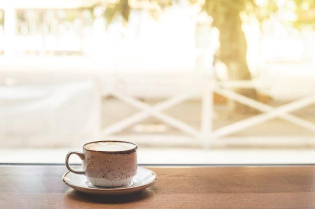 Eine kleine tasse cappuccino auf einem tisch am fenster.