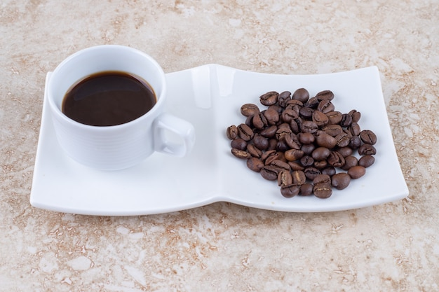 Eine kleine tasse kaffee neben einem haufen kaffeebohnen