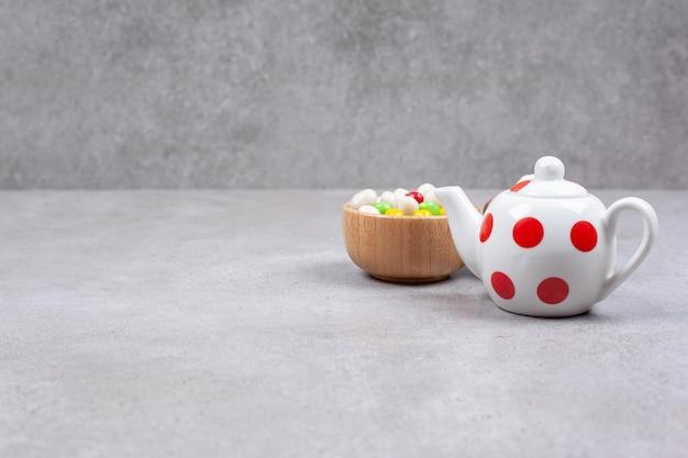Eine kleine teekanne mit einer schüssel süßigkeiten auf marmorhintergrund.