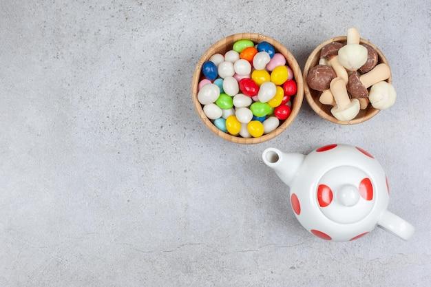 Eine kleine teekanne neben zwei schalen mit süßigkeiten und schokoladenpilzen auf marmoroberfläche