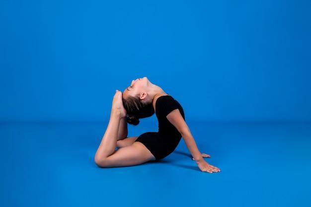 Eine kleine turnerin in einem schwarzen badeanzug macht flexibilitätsübungen auf blauem hintergrund mit einer kopie des raums