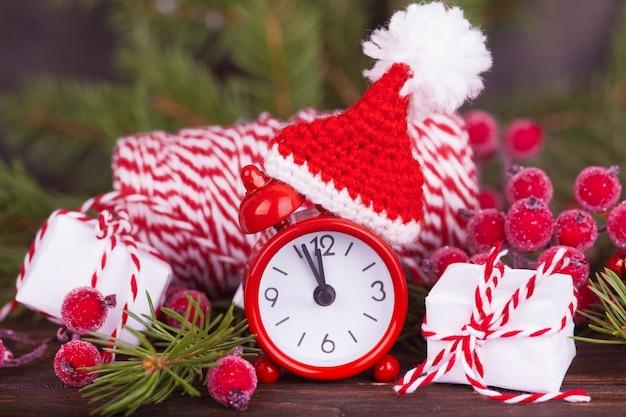 Eine kleine uhr in einer weihnachtsmütze, ein neujahrsgeschenk. weihnachtsdekoration.