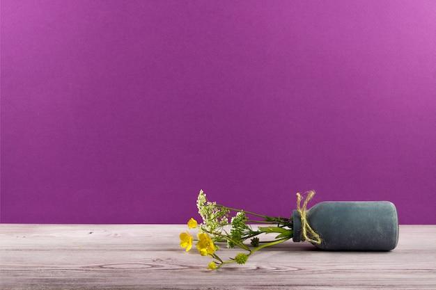 Eine kleine vase mit wildblumen liegt auf dem tisch
