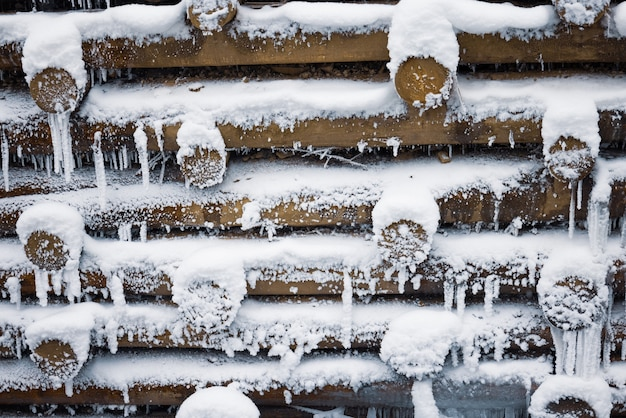 Eine kleine wand aus kleinen holzstämmen im winter unter schnee