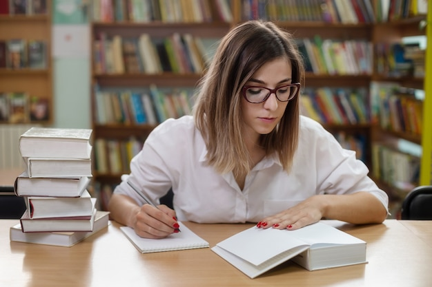 Eine kluge frau mit brille, die in der bibliothek mit büchern studiert