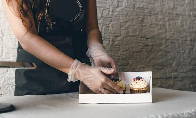 Eine köchin in einer grauen schürze packt cupcakes mit sahne in eine geschenkbox, um die bestellung an den kunden zu senden. backen zu hause.