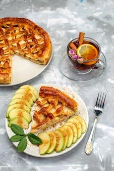 Eine köstliche apfelkuchenscheibe der draufsicht innerhalb der platte mit tee auf dem grauen schreibtischkuchen-kekszucker