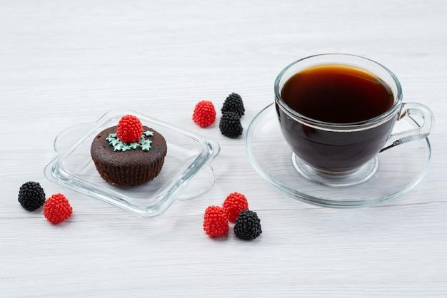 Eine köstliche braune vorderansicht zusammen mit frischen beeren und einer tasse tee auf weißen, bonbonfarbenen süßigkeiten