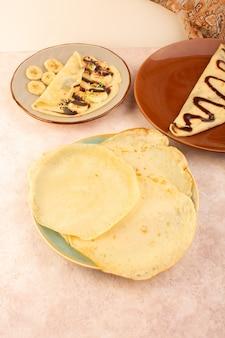 Eine köstliche dessertscheibe der draufsicht, die mit schokolade innerhalb der braunen und grünen runden platte auf dem rosa schreibtischnahrungsmittelmahlzeitdessertgebäck entworfen wird