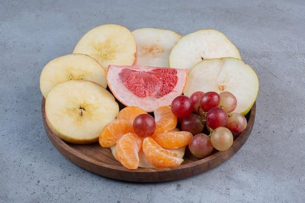 Eine köstliche frucht, die auf einem kleinen tablett auf marmorhintergrund dient.