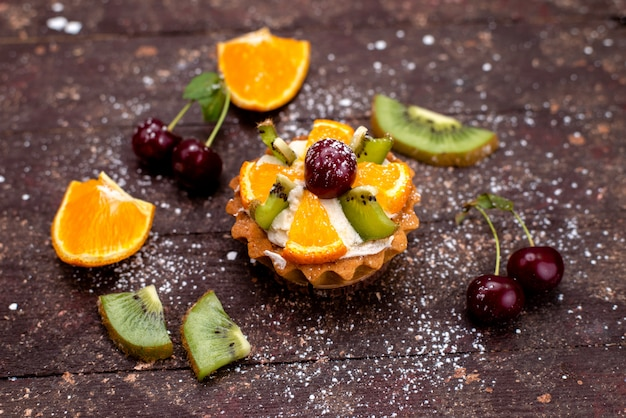 Eine köstliche kleine torte von oben mit sahne und frisch geschnittenen früchten auf den dunklen backgound-obstkuchen-keksen