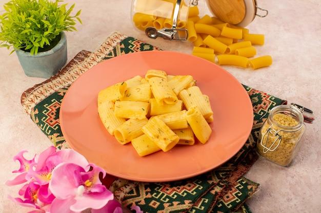 Eine köstliche mahlzeit der italienischen pasta der draufsicht innerhalb des rosa tellers zusammen mit rohen nudeln auf buntem teppich und rosa