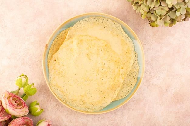 Eine köstliche pfannkuchen der draufsicht innerhalb des runden tellers auf dem rosa schreibtischnahrungsmittelmahlzeitdessertgebäck