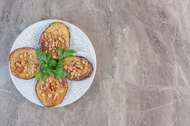 Eine köstliche portion indischer auberginen, gebraten und gewürzt mit knoblauch, geschmückt mit petersilie auf marmor. Kostenlose Fotos