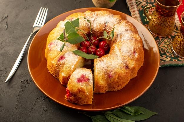 Eine köstliche runde gebackener obstkuchen der draufsicht mit roten kirschen innen und zuckerpulver innen runder brauner platte auf dunkelheit