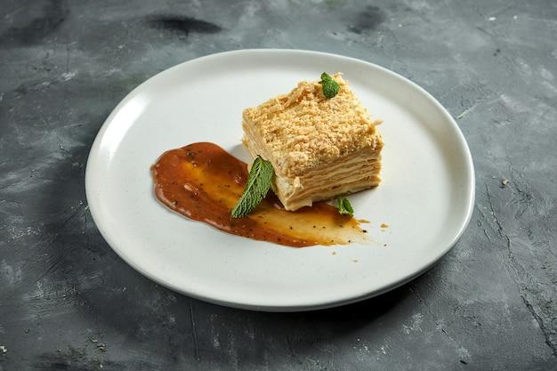 Eine köstliche scheibe französisches dessert mille-feuille mit schichten blätterteig und vanille- oder puddingscheibe, serviert in einem teller auf holzoberfläche