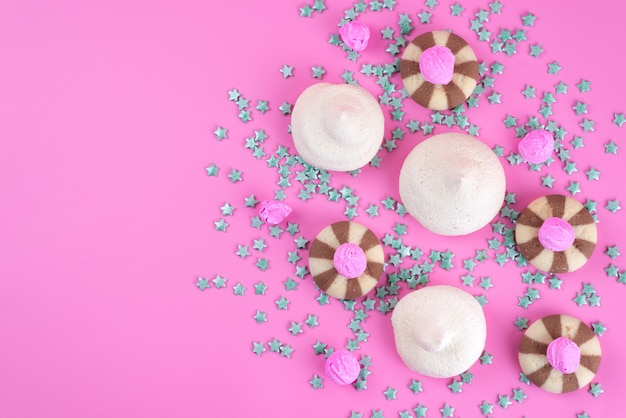 Eine köstliche und leckere schokoladenkekse von oben mit baisers auf rosa schreibtisch, keksfarbbonbon