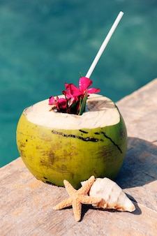 Eine kokosnuss mit trinkhalm am strand im sommer
