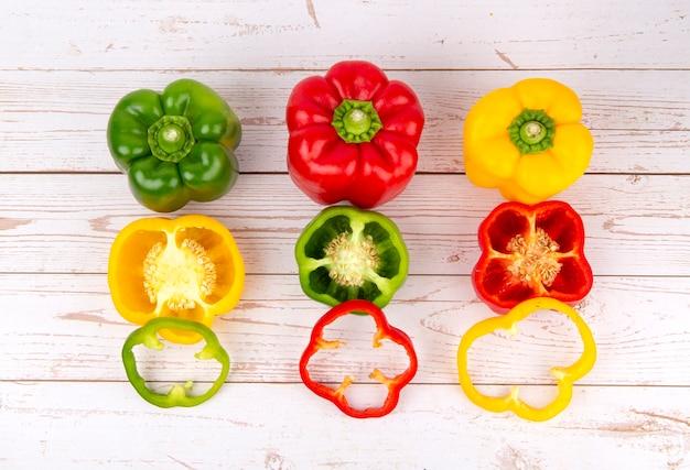 Eine kombination aus rotem gelbem und grünem paprika auf einem holztisch