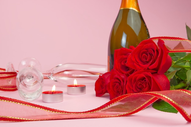 Eine komposition aus einem wunderschönen strauß rosen, kerzen, gläsern und einer flasche champagner schafft eine romantische karte. das konzept des valentinstags, muttertag, 8. märz.