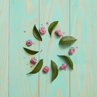 Eine komposition mit blättern und blüten in form eines runden rahmens mit einem platz unter dem text lag flach