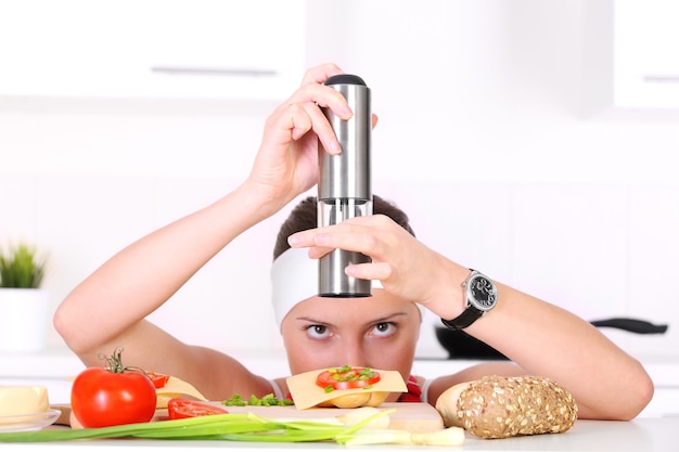 Eine konzentrierte frau, die in der küche ein sandwich mit petersilie würzt