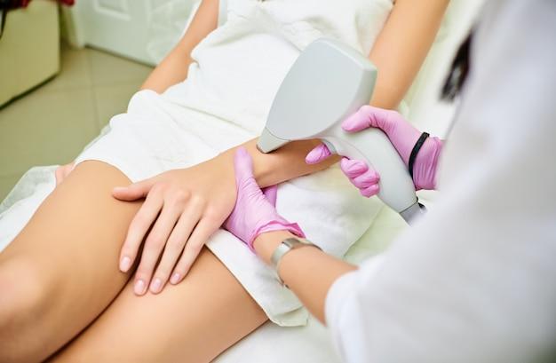 Eine kosmetikerin führt ein verfahren zur laserenthaarung aus dem körper eines mädchens durch. laser-haarentfernung. kosmologie. hand-haarentfernung