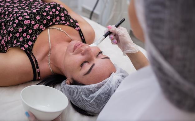 Eine kosmetikerin führt pflegeverfahren für einen kunden durch