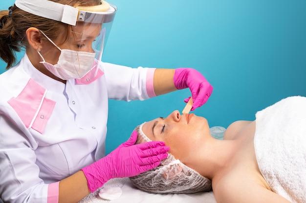 Eine kosmetikerin in einem weißen gewand, eine medizinische maske und ein schutzschirm machen kosmetische eingriffe schön