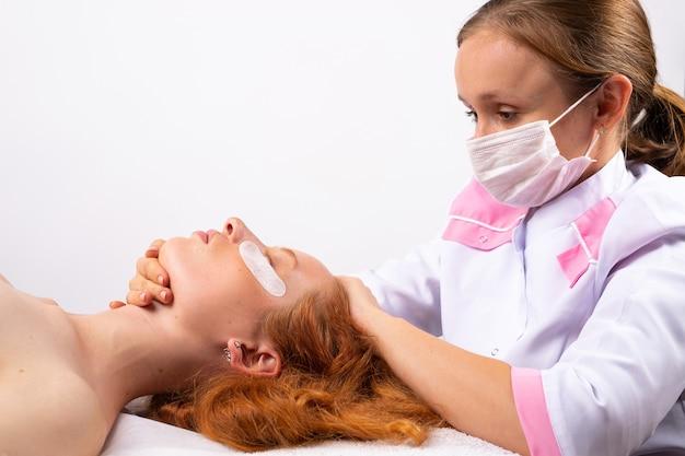 Eine kosmetikerin in einer medizinischen maske und einem weißen gewand macht einer rothaarigen frau eine gesichtsmassage